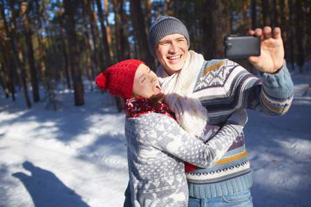 Young woman embracing her husband while he making their selfie in the park photo