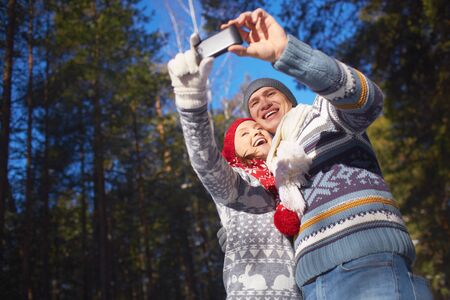 Modern couple with smartphone making selfie in natural environment photo