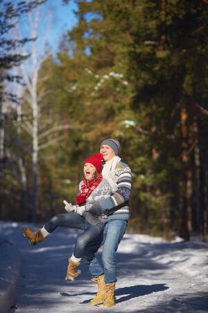 Happy young man holding his girlfriend while having fun photo