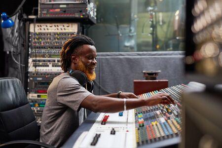 soundboard: Young sound-operator sitting by soundboard in audio studio Stock Photo