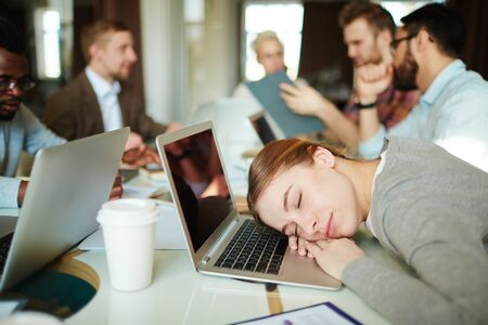 asleep: Tired businesswoman sleeping on laptop keypad in working environment