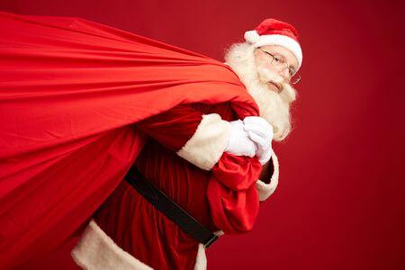 Santa carrying big red sack with xmas presents photo