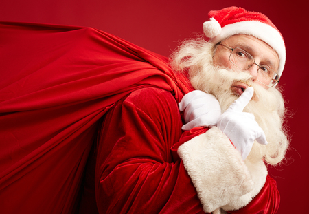 shh: Santa with heavy sack showing shh gesture Stock Photo