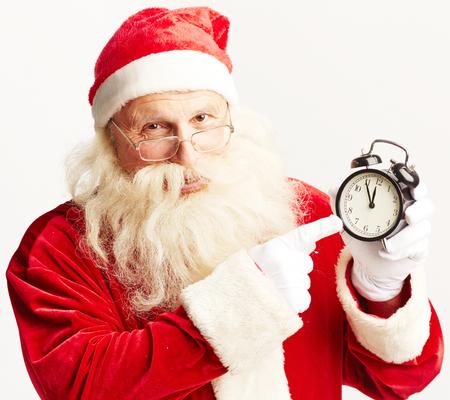 Santa showing time in alarm-clock and looking at camera photo