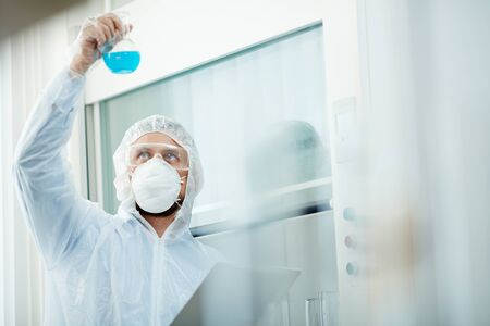 protective clothing: Scientific expert in protective clothing, eyeglasses and respirator looking at tube with toxic fluid substance