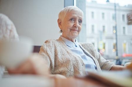 mujeres ancianas: de sexo femenino mayor bonita en ropa casual relajante en café Foto de archivo