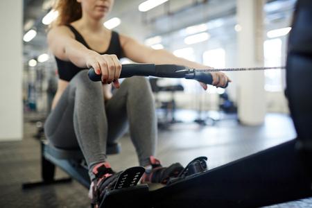 deportistas: Entrenamiento de la mujer joven en el remo-máquina en el gimnasio Foto de archivo
