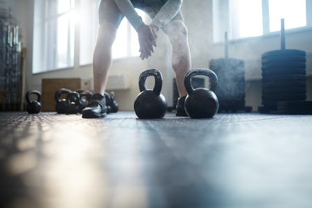 powerlifting: Two kettlebells on the gym floor and sportsman preparing his hands for powerlifting
