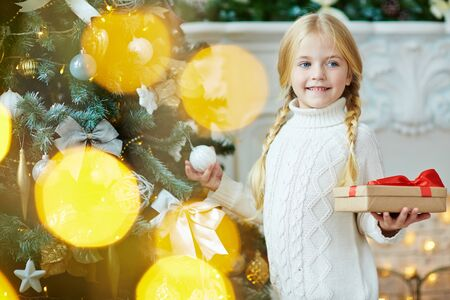 grandkid: Smiling child holding packed xmas gift while standing by decorated firtree
