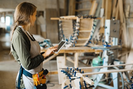 woodwork: Young owner of woodwork workshop searching for necessary data in the net