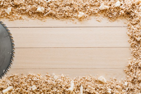 Backdrop of wooden board with sawdust and sawblade