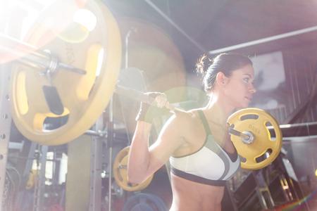 mujer de raza blanca de levantamiento de pesas en el gimnasio