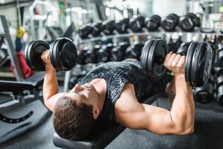 Sportivo sdraiato sulla cuccetta e bilancieri di sollevamento