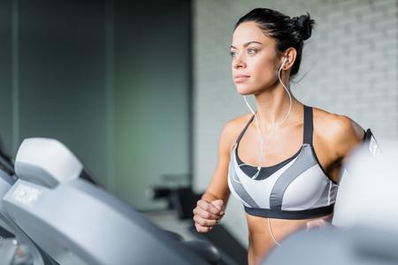 escucha activa: mujer joven con los auriculares que ejercita en gimnasia Foto de archivo