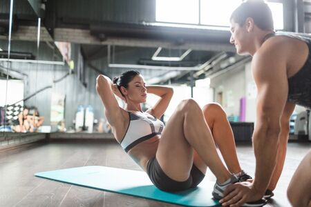 situp: Instructor helping young female during sit-up exercise Stock Photo