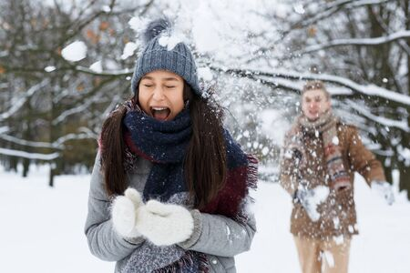 Ecstatic girl squealing from unexpected snowball thrown by her boyfriend