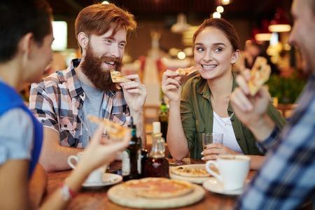 Amigos adolescentes felices comiendo pizza después de los estudios Foto de archivo - 66898096