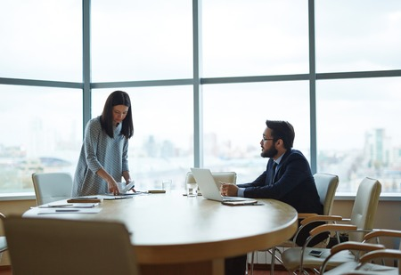 Director talking to his secretary in office before meeting with partners