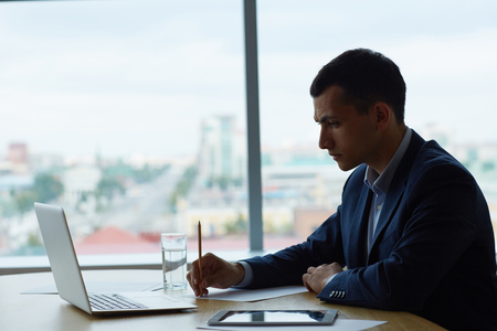 analyst: Serious analyst concentrating upon reading data Stock Photo