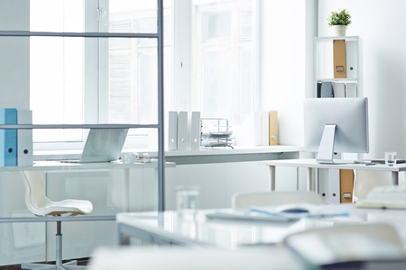Empty office with desks, computer, chair and stationary Stock Photo