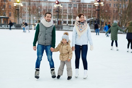 figureskating: Active couple and their daughter skating on ice-rink in urban environment