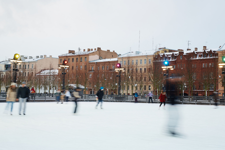 figureskating: Blurred human figures skating on ice-rink in urban environment Stock Photo