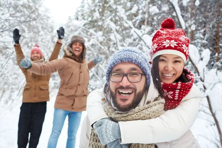 Asian couple in winterwear looking at camera and laughing