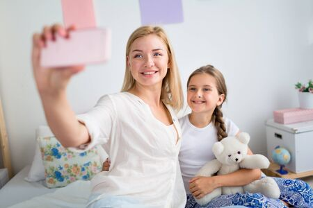 Mother and daughter making selfie at home photo