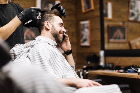 Happy businessman speaking on mobile phone during haircut