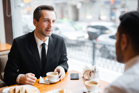 Confident advisor consulting his client in cafe Stock Photo