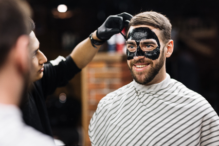 purifying: Man with purifying mask on his face looking in mirror while beautician applying it
