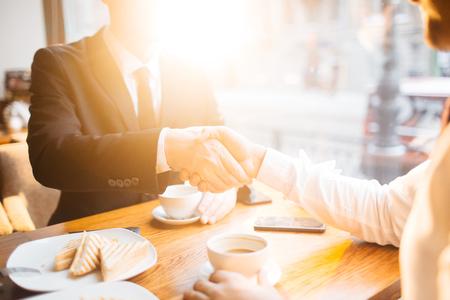 Zakenlieden handshaking in café tijdens de lunch