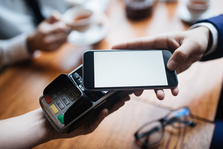 Businessman paying for lunch in cafe from smartphone