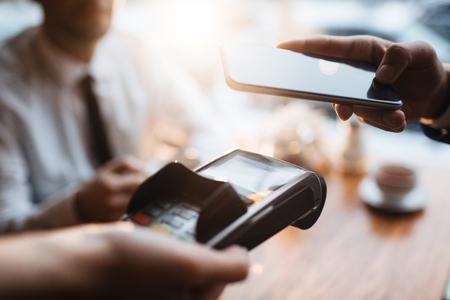 Comprador con el teléfono inteligente que paga a través del terminal