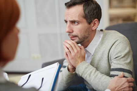 Stressed man visiting psychologist and sharing his problems