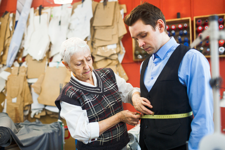 girth: Young businessman visiting atelier of private tailor Stock Photo