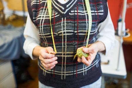 selfemployed: Self-employed tailor holding measuring tape Stock Photo