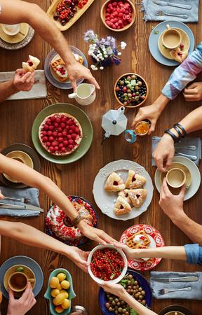 Menselijke handen over xmas tafel met vers dessert, omzet en bessen