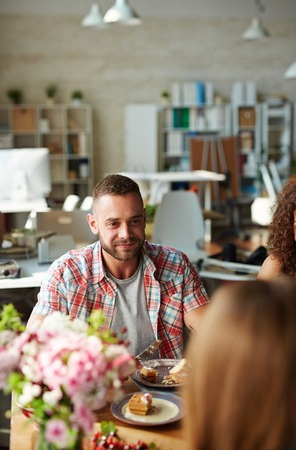 Handsome guy listening to friend while eating Stock Photo
