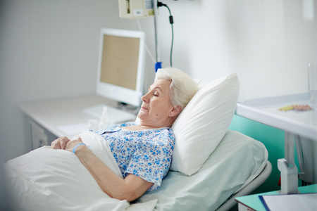 hospital patient: Retired patient lying in hospital bed Stock Photo