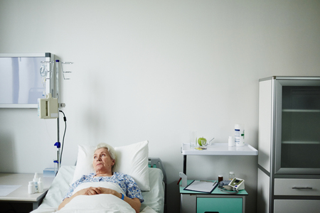 recuperation: Hospitalized female recovering from illness in bed Stock Photo