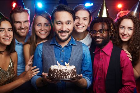 intercultural: Attractive Asian man holding birthday cake with burning candles among his intercultural friends Stock Photo