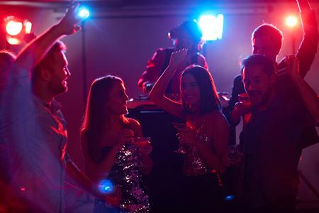 amis joyeux avec des cocktails parler et danser à la discothèque partie