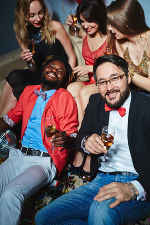 clubber: Elegant young men with champagne and happy girls relaxing at party