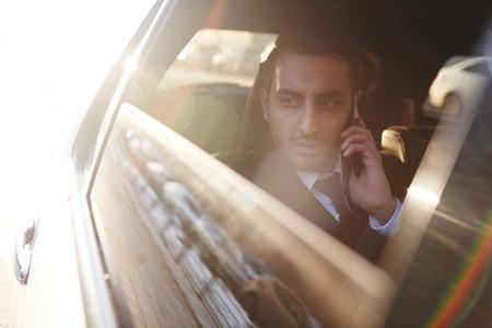 Ernster Geschäftsmann , der auf Smartphone beim Fahren durch Taxi spricht