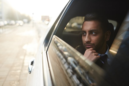 Rijke man kijkt door autoraam tijdens het reizen in de stad Stockfoto