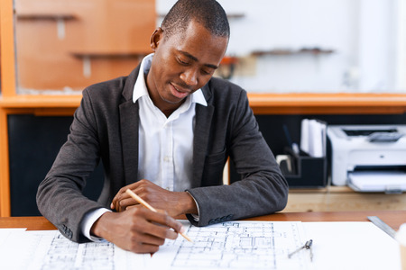 Young engineer drafting at workplace in office