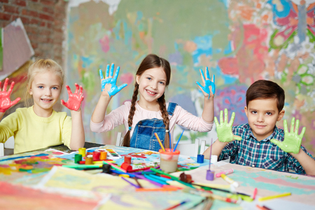niños estudiando: Niños con pintura en las palmas mirando a la cámara Foto de archivo