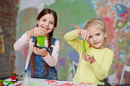 Twee vriendelijke meisjes met slijm plezier in de kleuterklas