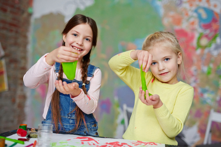 Two friendly girls with slime having fun in kindergarten